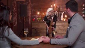 Θηλυκός μουσικός που εκτελεί ένα ρομαντικό τραγούδι για ένα ζεύγος σε ένα εστιατόριο φιλμ μικρού μήκους
