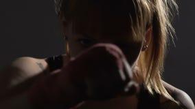 Θηλυκός μπόξερ που κάνει punching αέρα που εκπαιδεύει και που εξετάζει τη κάμερα, ανεξαρτησία φιλμ μικρού μήκους