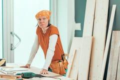 Θηλυκός ξυλουργός με την τοποθέτηση κορδελών στο εργαστήριο ξυλουργικής στοκ εικόνες