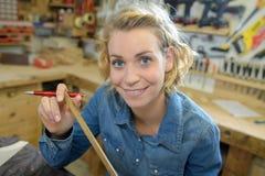 Θηλυκός ξυλουργός που εργάζεται με το ξύλο στο εργαστήριο Στοκ Εικόνα