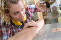 Θηλυκός ξυλουργός που εργάζεται στο woodboard στοκ εικόνα