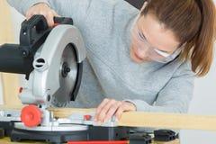 Θηλυκός ξυλουργός που χρησιμοποιεί το κυκλικό πριόνι Στοκ εικόνα με δικαίωμα ελεύθερης χρήσης