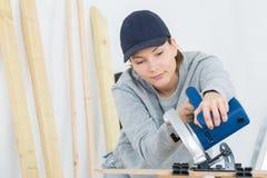 Θηλυκός ξυλουργός που χρησιμοποιεί το κυκλικό πριόνι Στοκ Φωτογραφίες