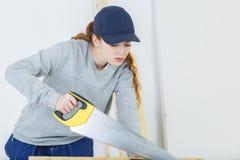 Θηλυκός ξυλουργός που χρησιμοποιεί το χειρωνακτικό πριόνι Στοκ εικόνες με δικαίωμα ελεύθερης χρήσης