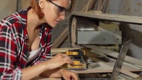 Θηλυκός ξυλουργός που χρησιμοποιεί το lap-top στο εργαστήριό της φιλμ μικρού μήκους