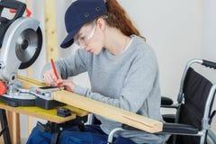 Θηλυκός ξυλουργός στην αναπηρική καρέκλα που χρησιμοποιεί το κυκλικό πριόνι Στοκ Φωτογραφίες