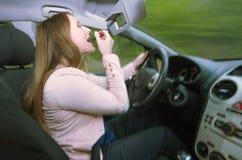 Θηλυκός οδηγός που χρησιμοποιεί το κραγιόν οδηγώντας Στοκ φωτογραφίες με δικαίωμα ελεύθερης χρήσης