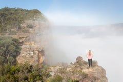 Θηλυκός οδοιπόρος που στέκεται σε μια πυραμίδα βράχου με την ομίχλη αύξησης από την κοιλάδα στοκ εικόνες