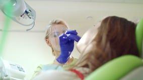Θηλυκός οδοντίατρος που βάζει tampon βαμβακιού στο ανοικτό υπομονετικό στόμα Διαδικασία επεξεργασίας απόθεμα βίντεο