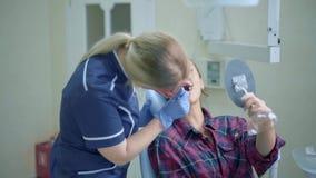 Θηλυκός οδοντίατρος που παρουσιάζει για το υπομονετικό αποτέλεσμα της θεραπείας φιλμ μικρού μήκους