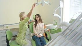 Θηλυκός οδοντίατρος που προετοιμάζει τον ασθενή για την εξέταση Εργασιακός χώρος στοματολογίας απόθεμα βίντεο