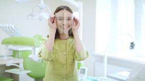 Θηλυκός οδοντίατρος που φορά τα γυαλιά ασφάλειας Ευτυχής φοιτητής Ιατρικής στην οδοντική κλινική απόθεμα βίντεο