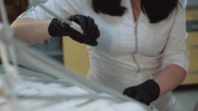 Θηλυκός οδοντίατρος που χρησιμοποιεί το ιατρικό εξοπλισμό για την επεξεργασία φιλμ μικρού μήκους