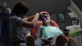 Θηλυκός οδοντίατρος στην εργασία Υπομονετικό αγόρι παιδιών στην οδοντική κλινική απόθεμα βίντεο