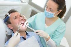 Θηλυκός οδοντίατρος στην κλινική με το υπομονετικό βάσανο Στοκ Φωτογραφίες