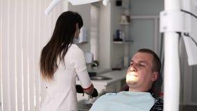 Θηλυκός οδοντίατρος Brunette που στέκεται από τον πίσω προετοιμαζόμενο αρσενικό ασθενή για την οδοντική θεραπεία να προετοιμαστεί φιλμ μικρού μήκους