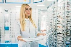 Θηλυκός οπτικός με τον κατάλογο γυαλιών στα χέρια στοκ εικόνα