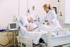 Θηλυκός παθολόγος που ρυθμίζει την αναπνευστική υποστήριξη στεμένος δίπλα στον ασθενή Στοκ φωτογραφία με δικαίωμα ελεύθερης χρήσης