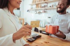 Θηλυκός πελάτης καφέ που κρατά μια χρυσή κάρτα Στοκ εικόνες με δικαίωμα ελεύθερης χρήσης