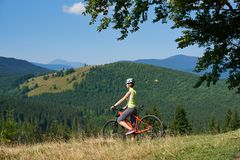 Θηλυκός ποδηλάτης στο κράνος που στέκεται με το κόκκινο ποδήλατο στο χλοώδη λόφο Στοκ εικόνες με δικαίωμα ελεύθερης χρήσης
