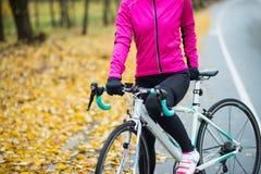 Θηλυκός ποδηλάτης στο ρόδινο σακάκι που στηρίζεται με το οδικό ποδήλατο στην κρύα ηλιόλουστη ημέρα φθινοπώρου στοκ εικόνες