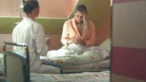 Θηλυκός πολυφυλετικός γιατρός που δίνει την ιατρική και το νερό στον ασθενή της φιλμ μικρού μήκους