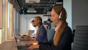 Θηλυκός πράκτορας χειριστών με τις κάσκες που λειτουργούν σε ένα κέντρο κλήσης φιλμ μικρού μήκους