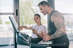 θηλυκός προσωπικός εκπαιδευτής που δείχνει treadmill στην οθόνη και τον τρέχοντας αθλητικό τύπο στοκ εικόνα
