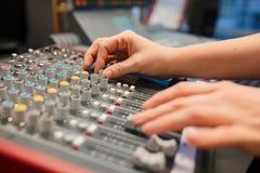 Θηλυκός ραδιο οικοδεσπότης που χρησιμοποιεί τον αναμίκτη μουσικής στο στούντιο στοκ εικόνες