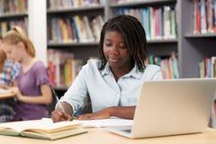 Θηλυκός σπουδαστής γυμνασίου που εργάζεται στο lap-top στη βιβλιοθήκη στοκ εικόνες
