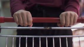 Θηλυκός στενός επάνω χεριών με το κάρρο αγορών φιλμ μικρού μήκους