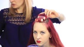 Θηλυκός στιλίστας που δημιουργεί το τέλειο hairstyle με τις μεγάλες μπούκλες για τη νέα redhead γυναίκα φιλμ μικρού μήκους