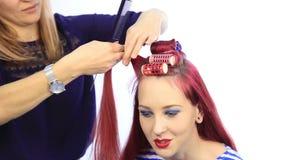 Θηλυκός στιλίστας που δημιουργεί το τέλειο hairstyle με τις μεγάλες μπούκλες για τη νέα redhead γυναίκα απόθεμα βίντεο