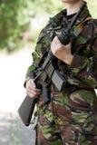 Θηλυκός στρατιώτης με ένα πυροβόλο όπλο στη φρουρά Στοκ Φωτογραφίες
