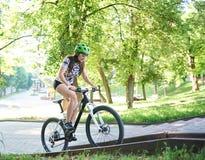 Θηλυκός στρωμένη ποδηλάτων ποδηλατών οδηγώντας επάνω λόφος στοκ φωτογραφία