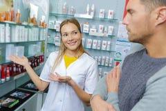 Θηλυκός συμβουλευτικός πελάτης φαρμακοποιών για τη χρήση φαρμάκων στοκ εικόνες με δικαίωμα ελεύθερης χρήσης