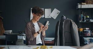 Θηλυκός σχεδιαστής μόδας που χρησιμοποιεί το smartphone κατά τη διάρκεια του σπασίματος στο χαμόγελο εργασίας απόθεμα βίντεο