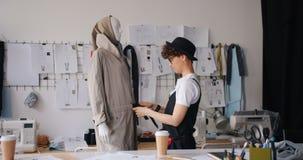Θηλυκός σχεδιαστής που βάζει το ένδυμα στο μανεκέν που εργάζεται στο σύγχρονο στούντιο απόθεμα βίντεο