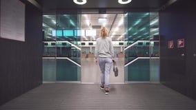 Θηλυκός ταξιδιώτης επιβατών που ελέγχει τις πληροφορίες του εισιτηρίου περασμάτων τροφής και για τον πίνακα προγράμματος που προε φιλμ μικρού μήκους