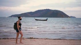 Θηλυκός ταξιδιώτης με το σακίδιο πλάτης που θαυμάζει μια θαλάσσια άποψη που φορά την ιατρική ενάντια στο νέφος μάσκα απόθεμα βίντεο