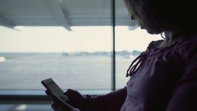 Θηλυκός τουρίστας που διαβάζει το σε απευθείας σύνδεση βιβλίο, περιμένοντας την πτήση, χρόνος εξόδων στον αερολιμένα φιλμ μικρού μήκους