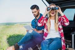 θηλυκός τουρίστας που κοιτάζει μέσω των διοπτρών ενώ ο φίλος της στοκ εικόνες με δικαίωμα ελεύθερης χρήσης