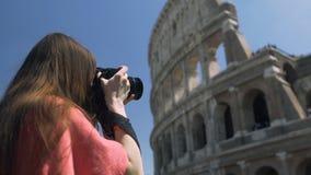Θηλυκός τουρίστας που χρησιμοποιεί τη κάμερα για να πάρει τη φωτογραφία Coliseum, που απολαμβάνει το χόμπι στον ελεύθερο χρόνο φιλμ μικρού μήκους