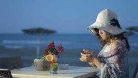Θηλυκός τουρίστας που χρησιμοποιεί το smartphone, δακτυλογραφώντας το μήνυμα στον καφέ παραλιών με την άποψη θάλασσας απόθεμα βίντεο