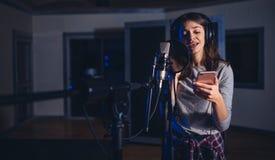 Θηλυκός τραγουδιστής αναπαραγωγής ήχου με το κινητό τηλέφωνο Στοκ φωτογραφίες με δικαίωμα ελεύθερης χρήσης
