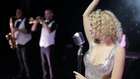 Θηλυκός τραγουδιστής με μια ζώνη στη σκηνή απόθεμα βίντεο
