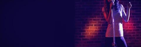 Θηλυκός τραγουδιστής που αποδίδει ενάντια στον τοίχο στη λέσχη Στοκ Εικόνα