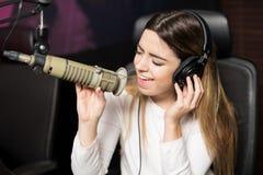 Θηλυκός τραγουδιστής που εκτελεί το ζωντανό τραγούδι στο ραδιοσταθμό Στοκ Εικόνες