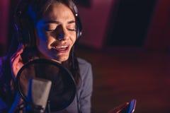 Θηλυκός τραγουδιστής που καταγράφει ένα τραγούδι στο στούντιο Στοκ φωτογραφία με δικαίωμα ελεύθερης χρήσης