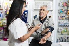 Θηλυκός φαρμακοποιός που ελέγχει τη πίεση του αίματος του ανώτερου ατόμου στοκ φωτογραφίες με δικαίωμα ελεύθερης χρήσης